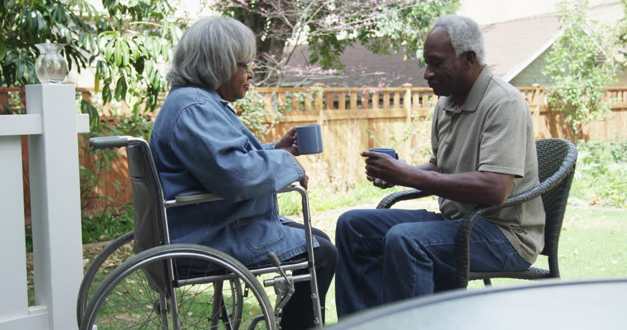 An older man seated in a chair speaks with an older woman in a wheelchair.