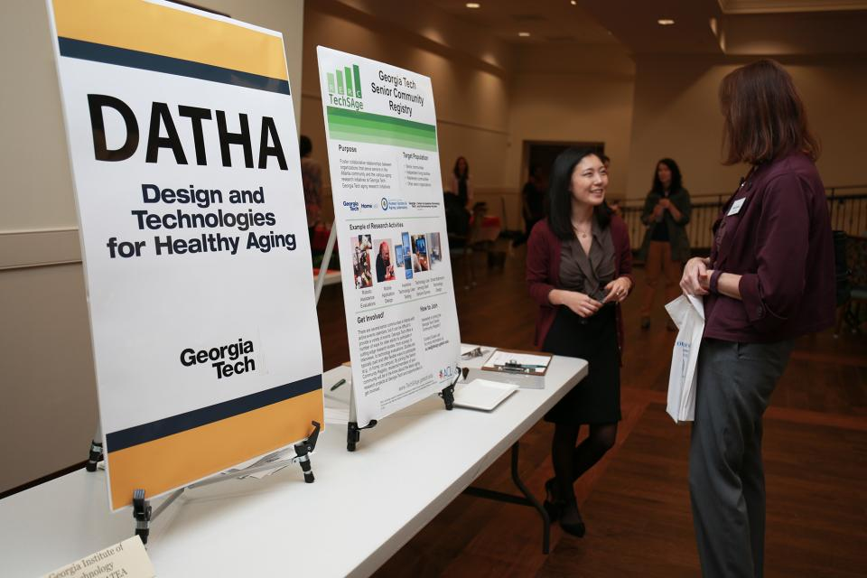 Two people talk next to a table with signage about design and technology for healthy aging.