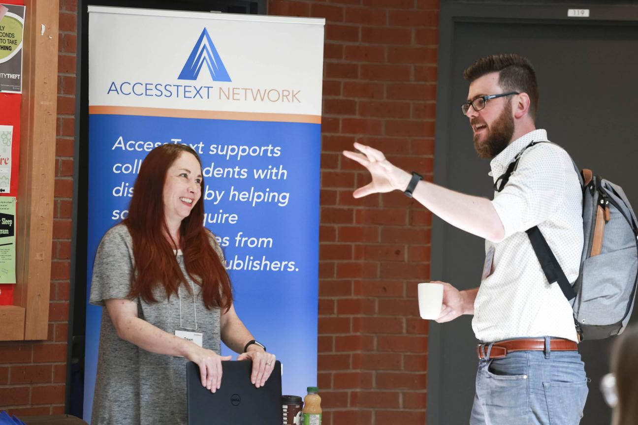 A woman, left, and man, right stand in discussion beneath an accessibility banner.