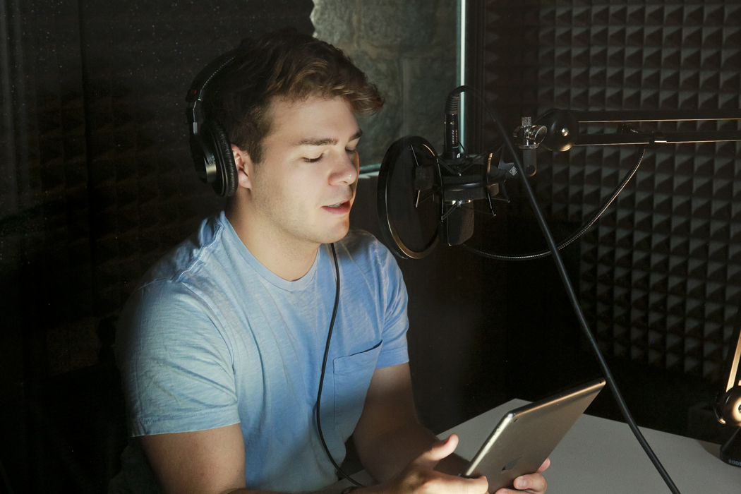 A man in an audio booth speaks into a microphone.
