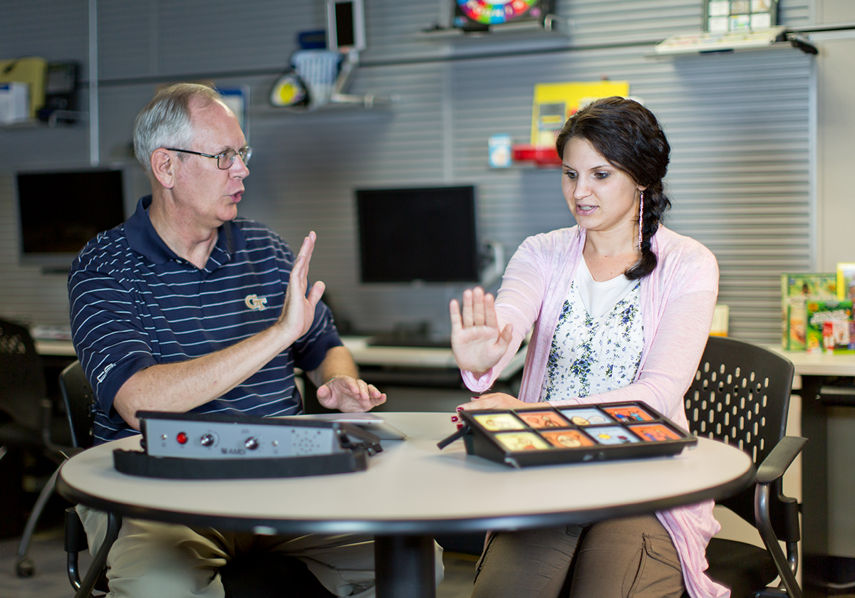 An older man demonstrating how to use assistive technology to a young woman.