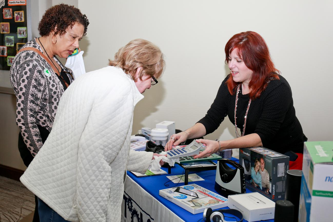 A woman showing two people how to use assistive technology.