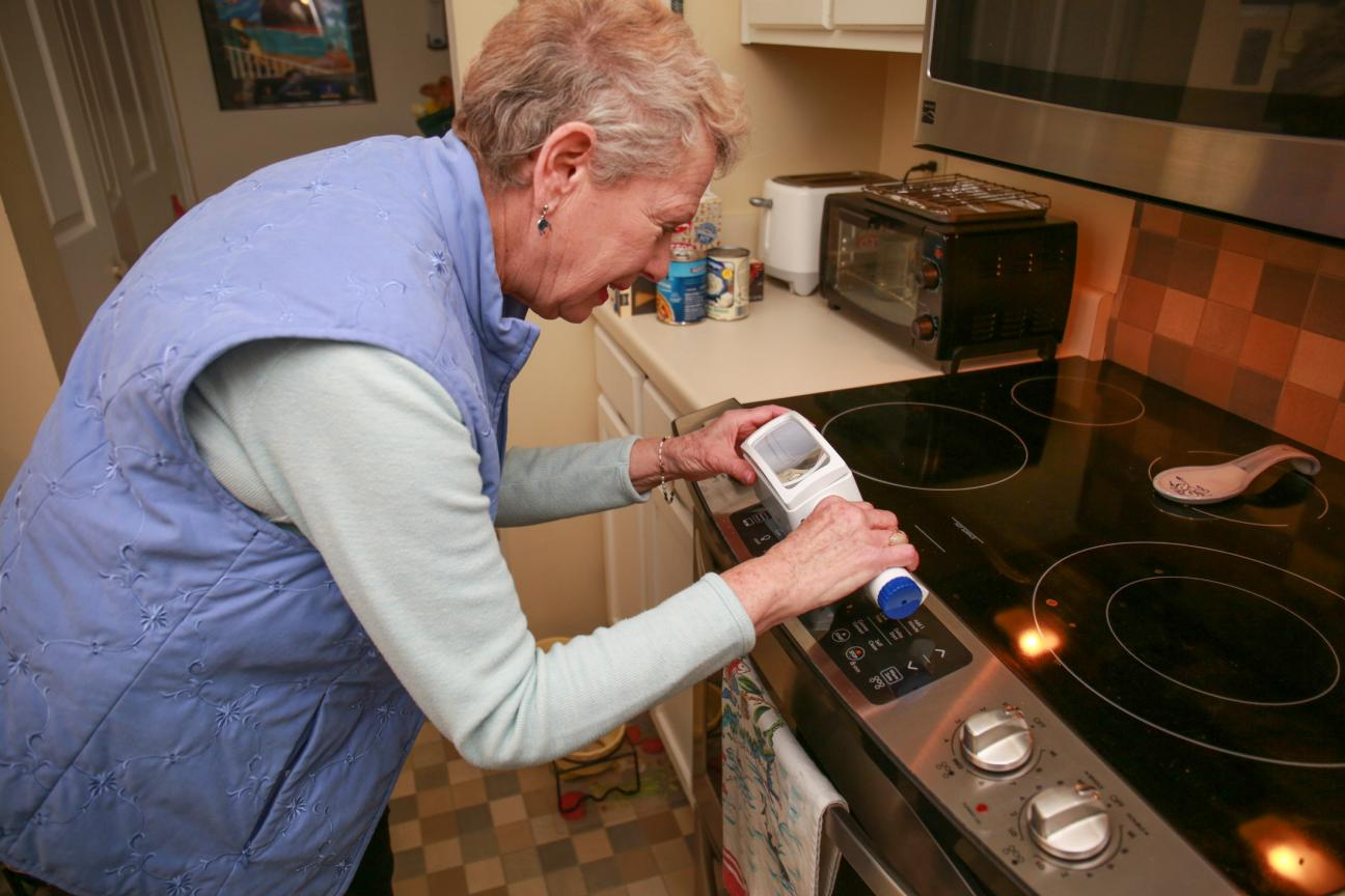 An older woman uses a tool at a stove.
