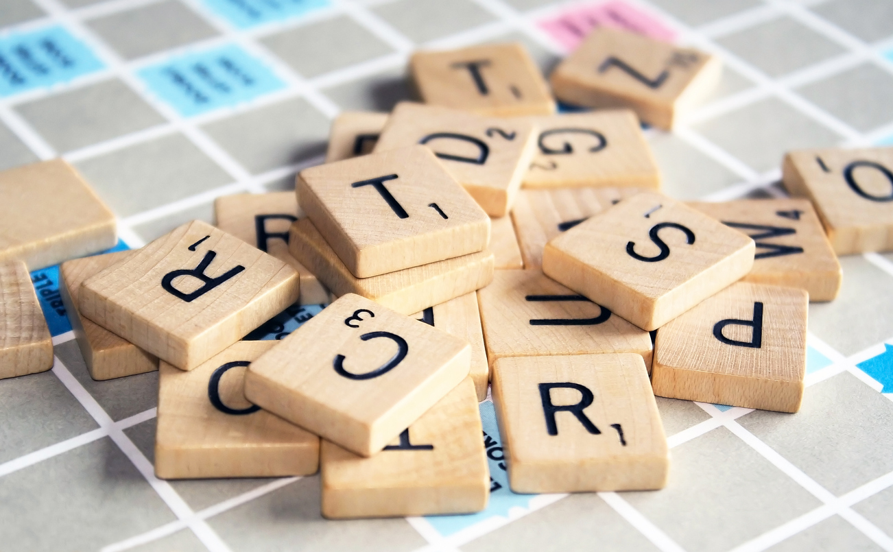 Scrabble tiles are shown scattered on a game board.
