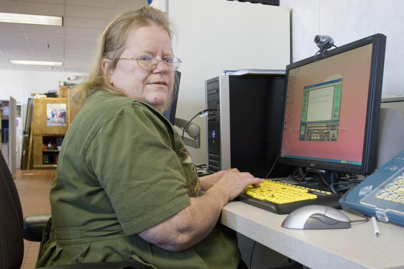 Woman using high contrast keyboard for accessibility at work.