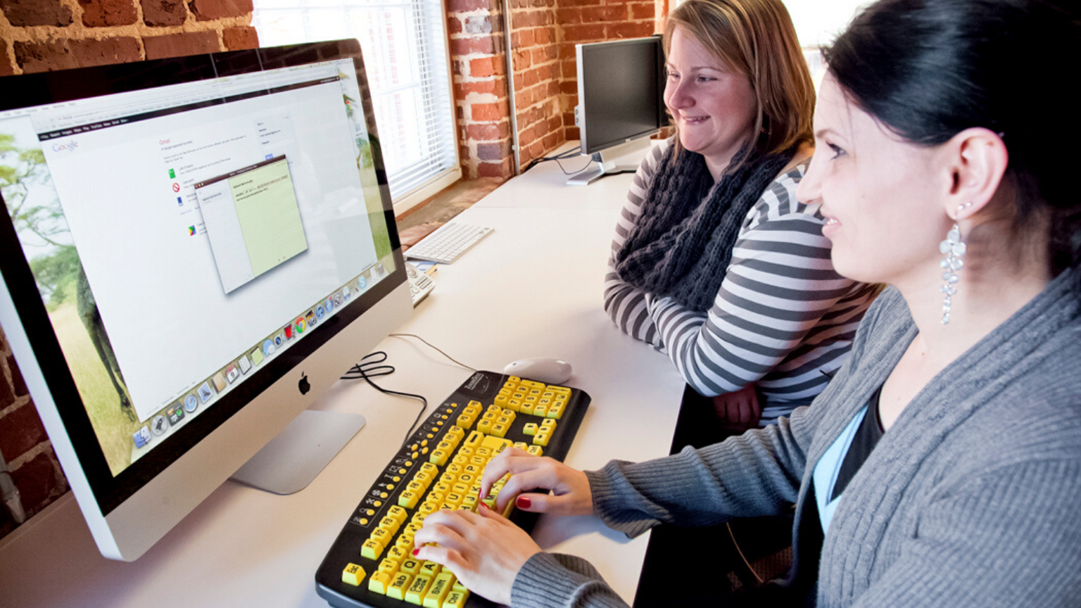 Two women using a computer with a high contrast keyboard