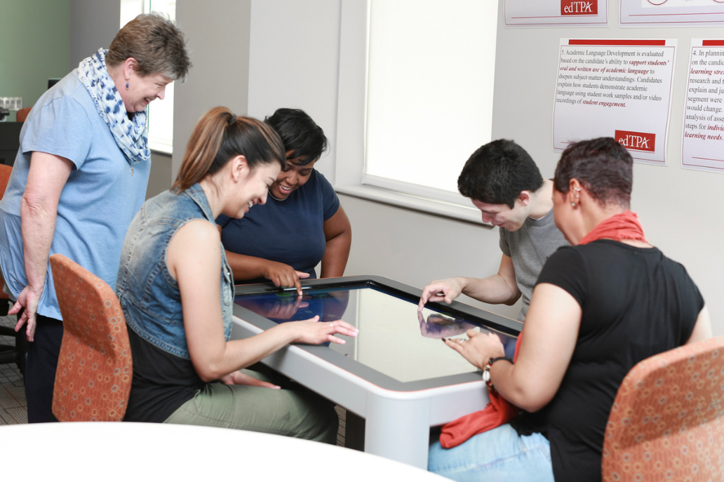 A group of students in a community center using assistive technology.
