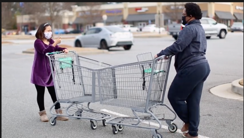 Two teenagers practicing social distancing by using two shopping carts nose to nose to measure 6 feet.